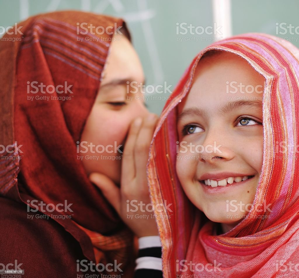 Two young girls in hijab whispering and giggling royalty-free stock photo