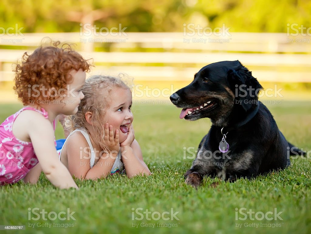 Two Young Girls Laying Near Black Family Pet Dog royalty-free stock photo