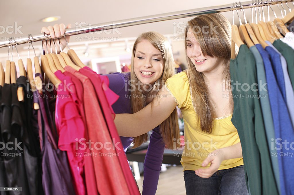 Two young girls looking through shirt rack in clothing store royalty-free stock photo