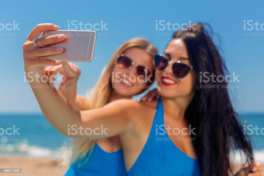 Two young girls making selfie on beach at summertime stock photo