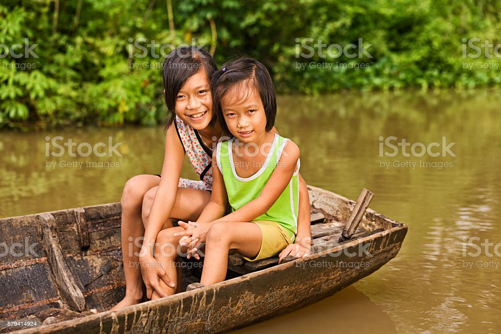 Two young girls on boat in Mekong River Delta, Vietnam stock photo
