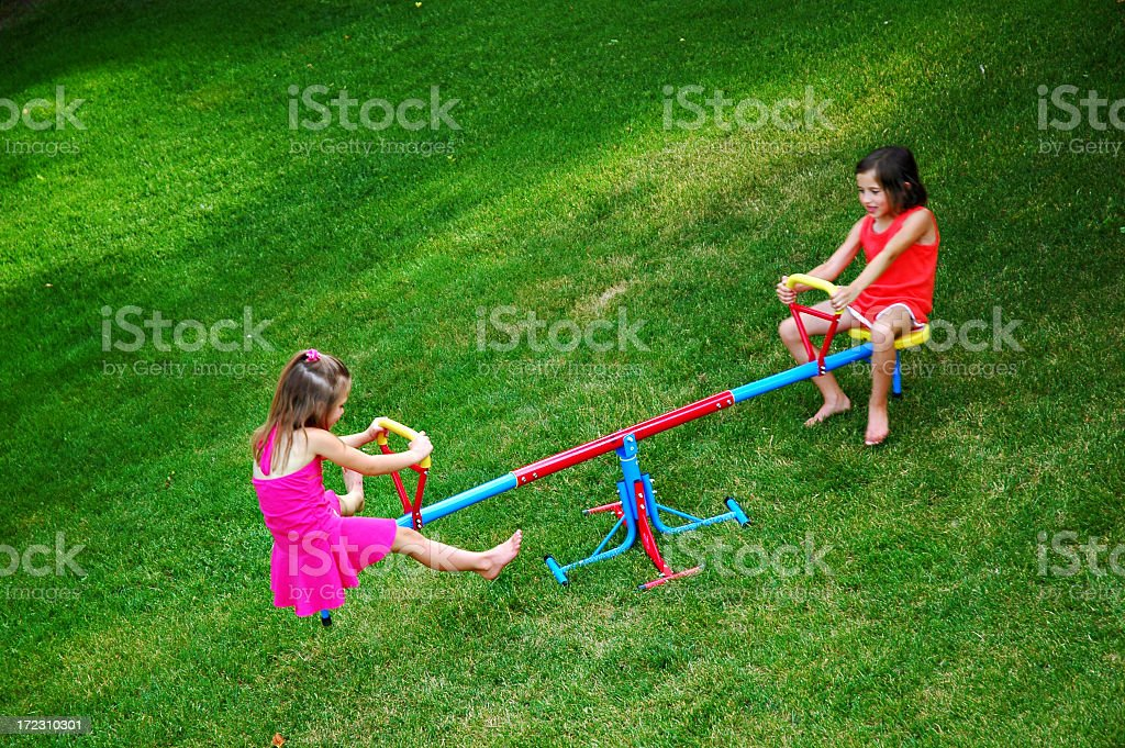 Two young girls on colorful teeter totter in green grass stock photo