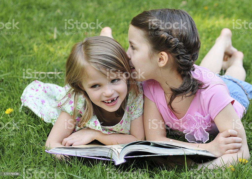 Two young girls on grass reading book whispering stock photo