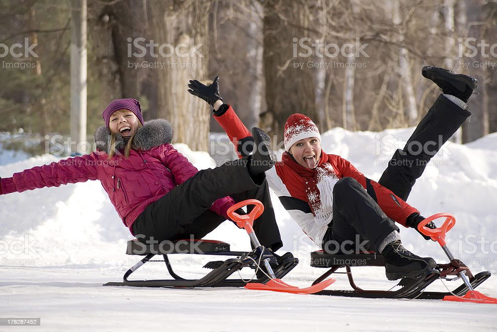 Two young girls on little snowmobiles royalty-free stock photo