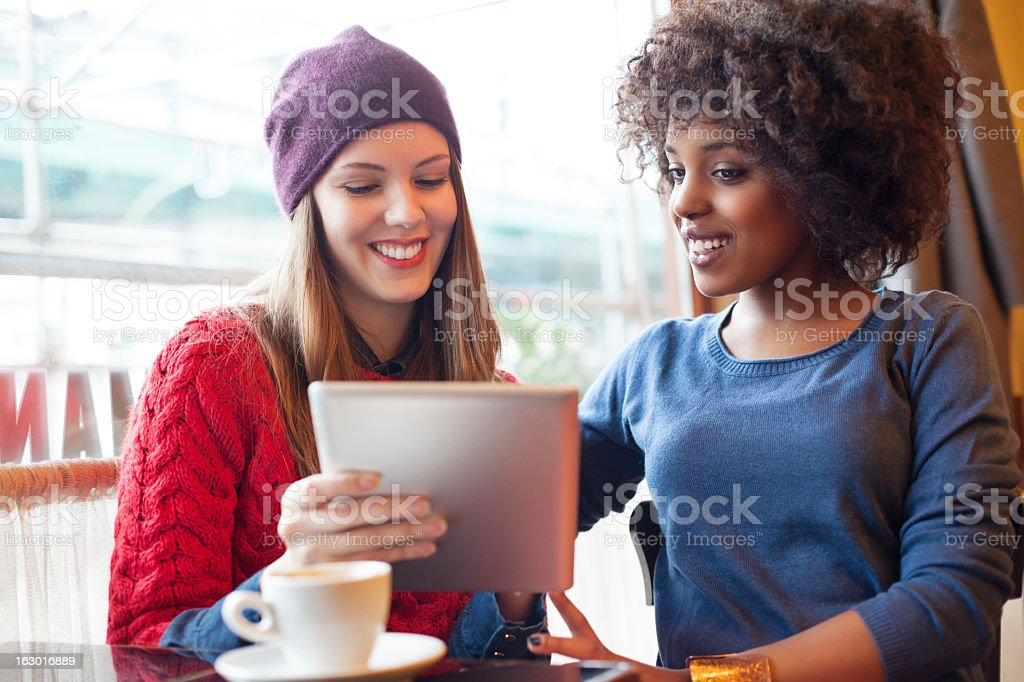 Two young girls photographing with a digital tablet royalty-free stock photo