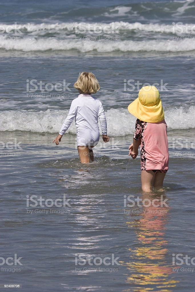 Two Young Girls Play in Waves, Beach, Sun Hat, Cute royalty-free stock photo