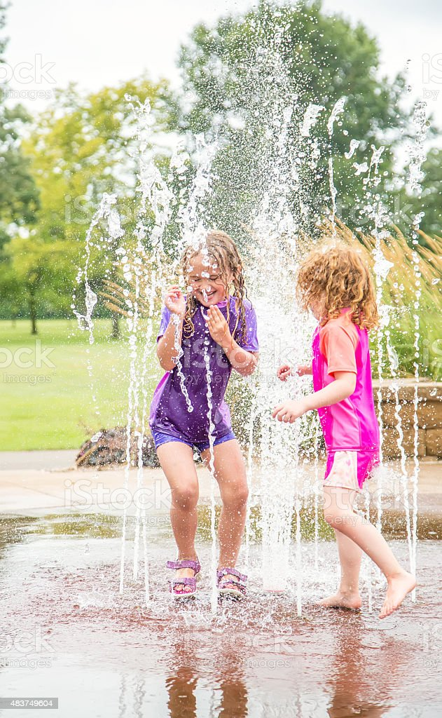 Two Young Girls Playing in Summer Fountains at Splash Park stock photo