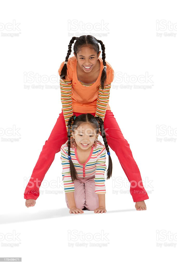 Two young girls playing leap frog indoors stock photo