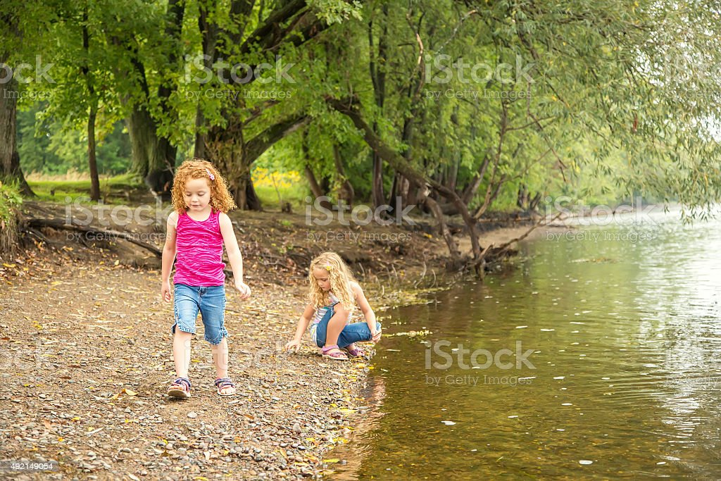 Two Young Girls Playing On Bank of Mississippi River stock photo