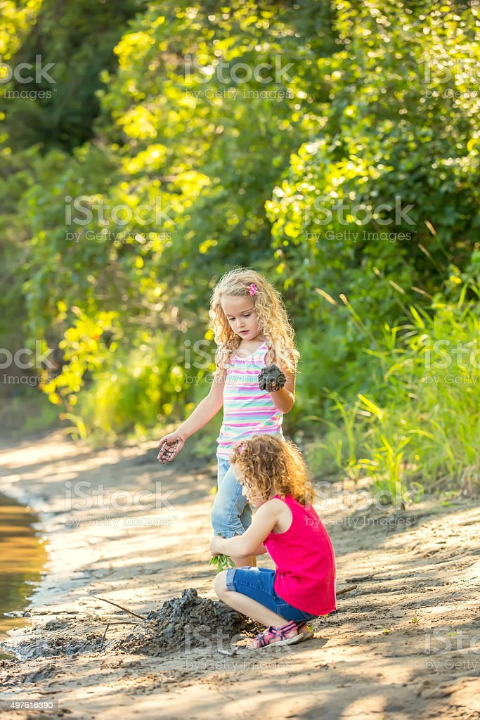 Two Young Girls Playing on Riverbank in Late Summer stock photo