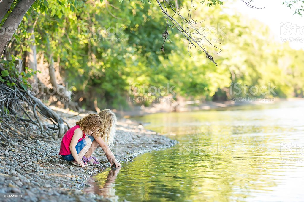 Two Young Girls Playing on Riverbank stock photo