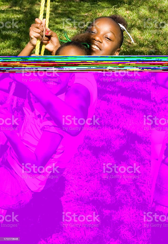 Two young girls playing on the swings royalty-free stock photo