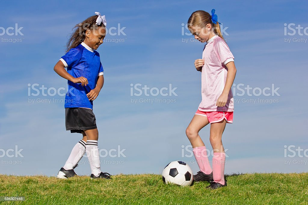 Two young girls playing soccer stock photo