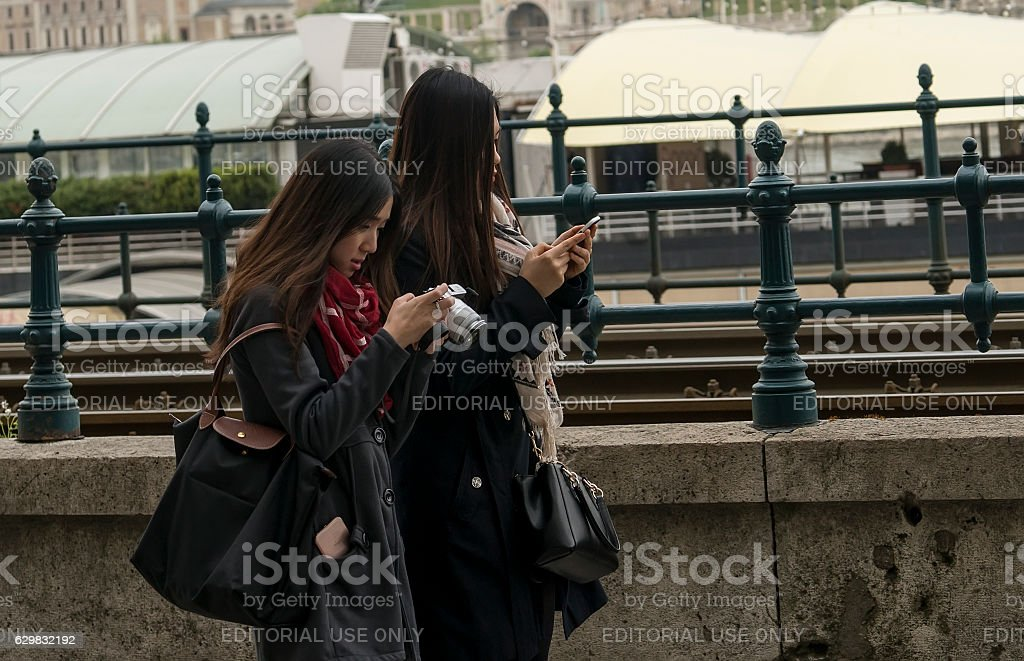 Two young girls playing with mobile phones stock photo