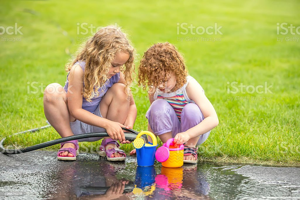 Two Young Girls Playing With Water stock photo