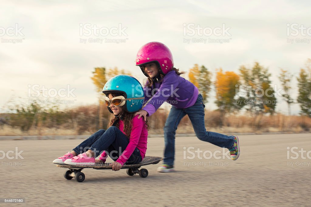 Two Young Girls Race on Skateboard stock photo