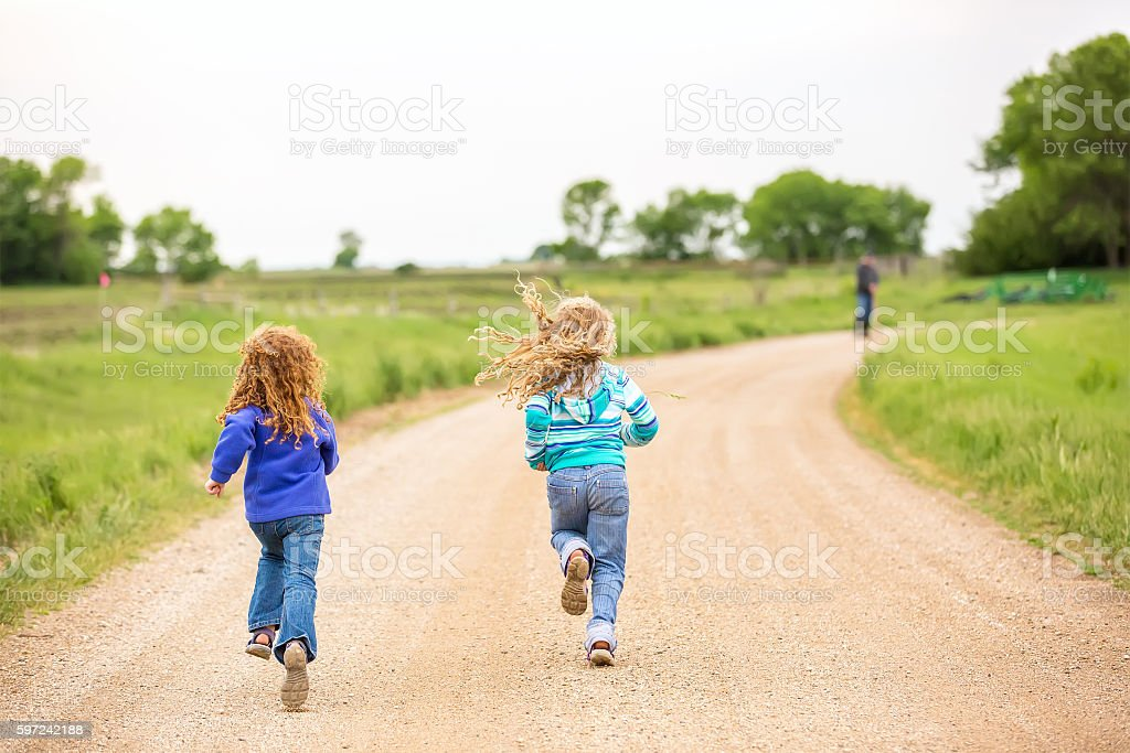 Two Young Girls Running Down Rural Gravel Driveway stock photo
