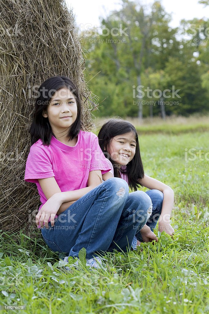 Two young girls sitting against haybale royalty-free stock photo