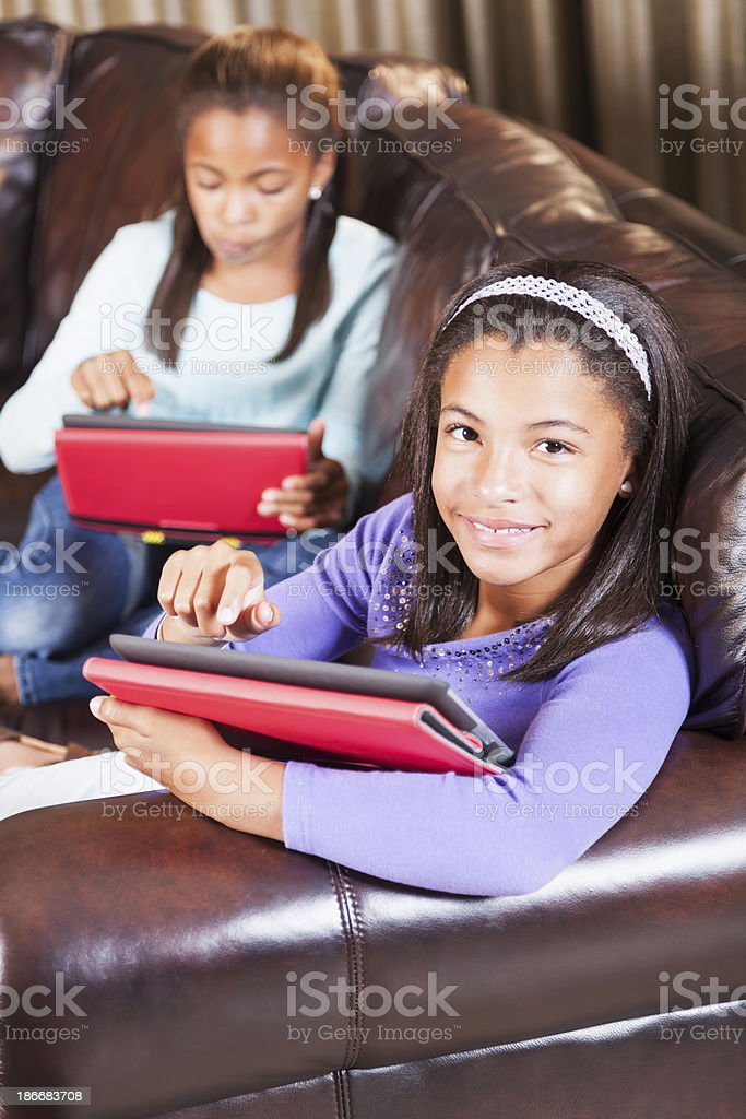 Two young girls sitting on couch using digital tablets stock photo