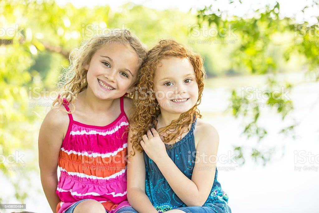Two Young Girls Sitting on Riverbank Smiling at Camera stock photo