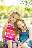 Two Young Girls Sitting on Riverbank Smiling at Camera