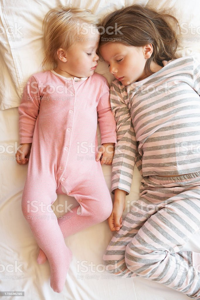 Two Young Girls Sleeping In Bed stock photo