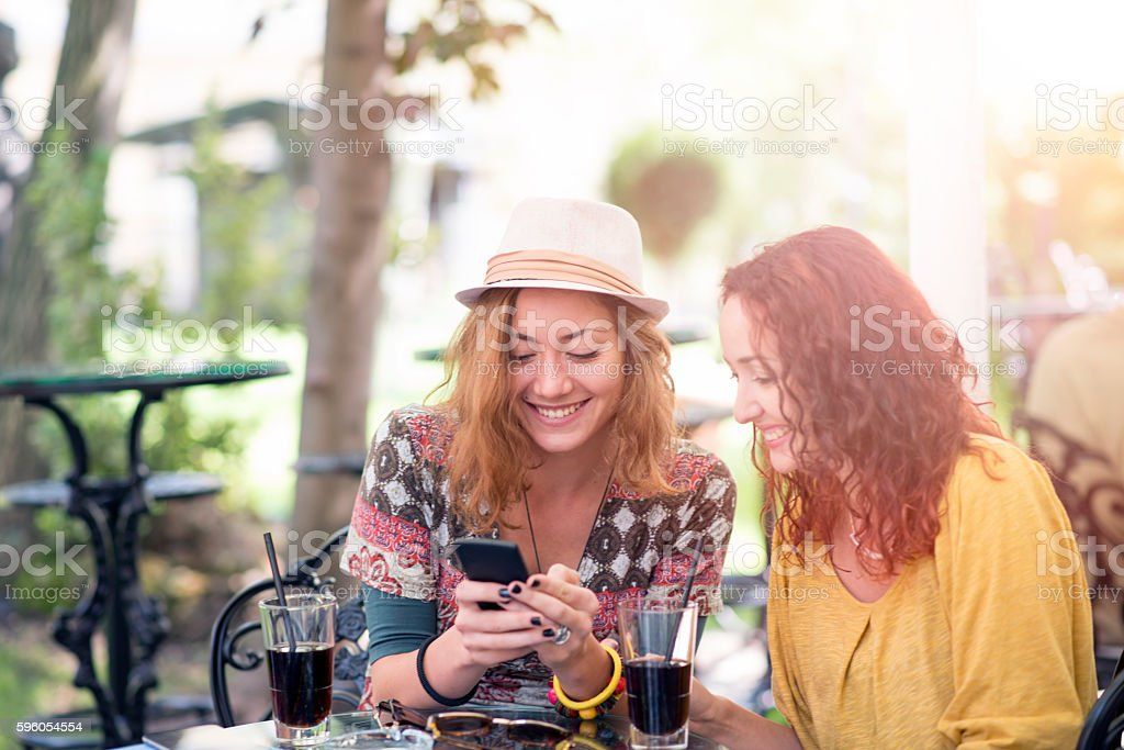 Two young girls smiling using smart phone in a cafe stock photo