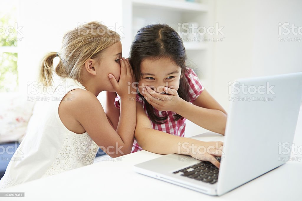 Two Young Girls Using Laptop At Home And Whispering stock photo