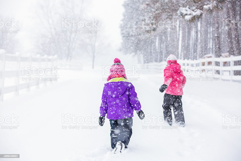 Two Young Girls Walking in Winter Snow Storm stock photo