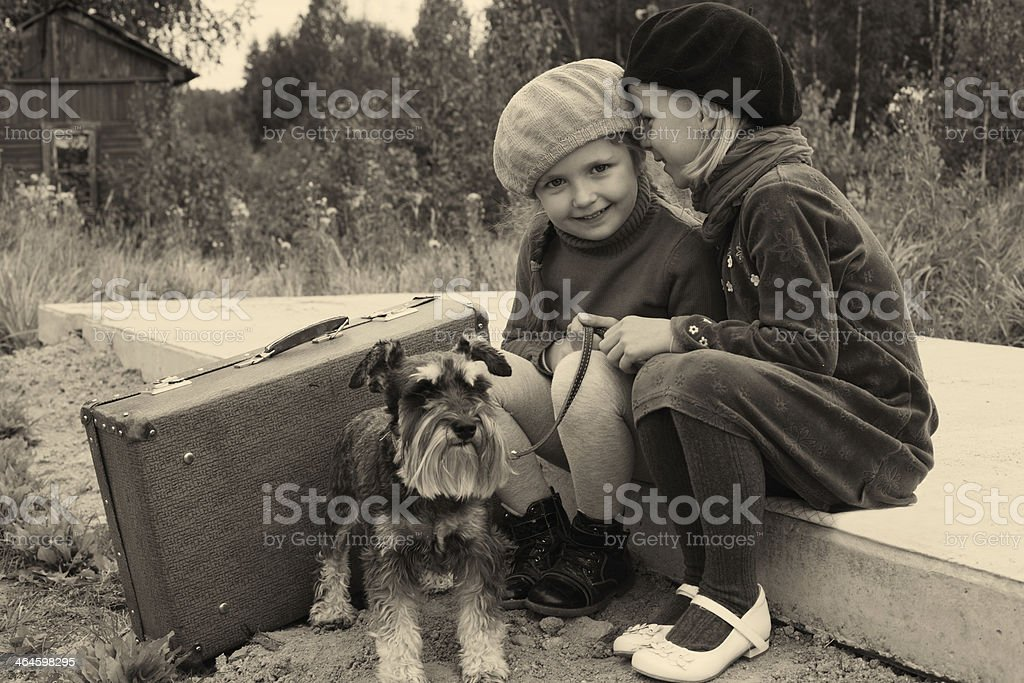 Two young girls with dog at bus stop stock photo