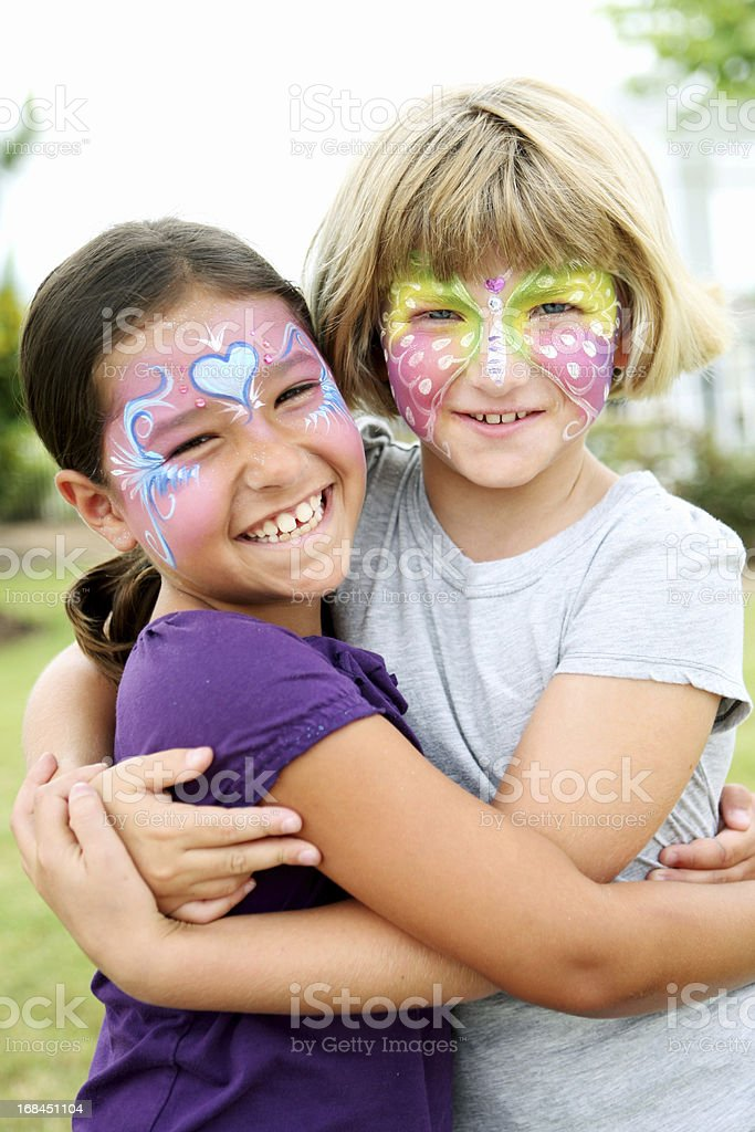 Two young girls with their faces painted stock photo