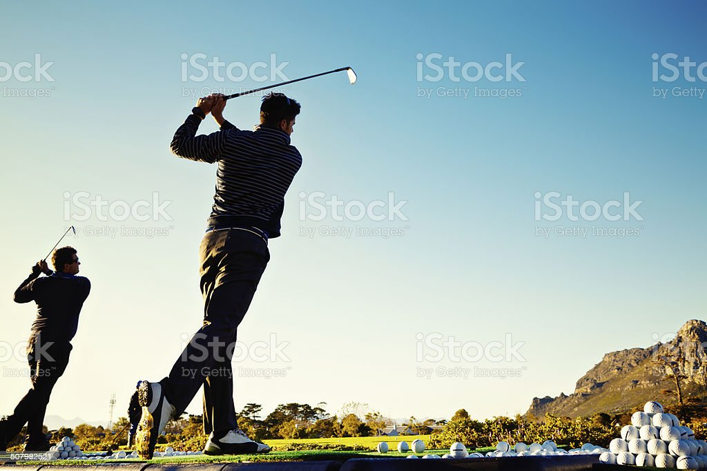 Two young golfers practising at a driving range stock photo