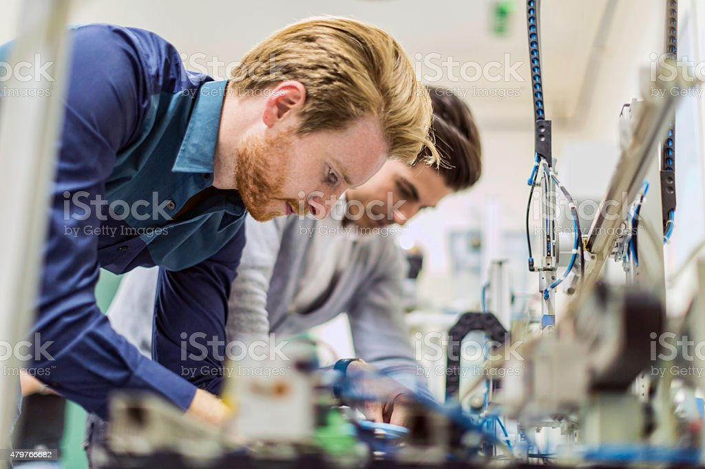 Two young handsome engineers working on electronics components stock photo