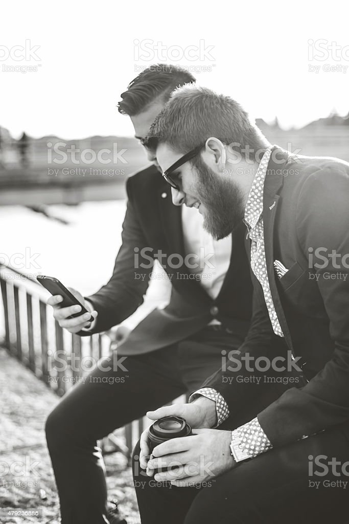 Two young hipster business man looking offer at their smartphone. stock photo