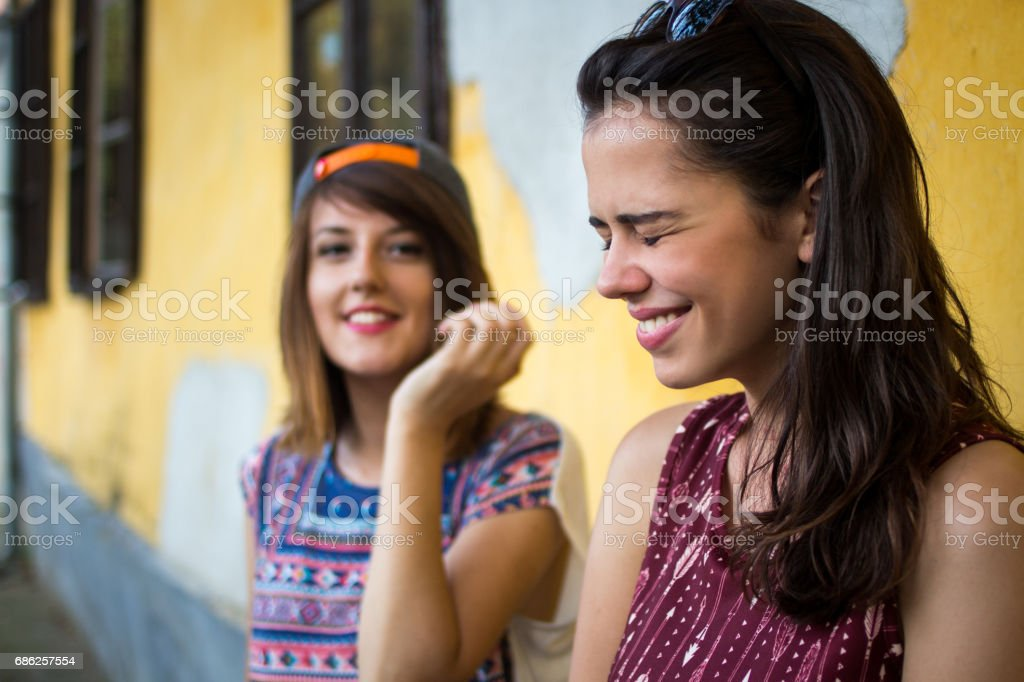 Two young hipster girls against yellow wall stock photo