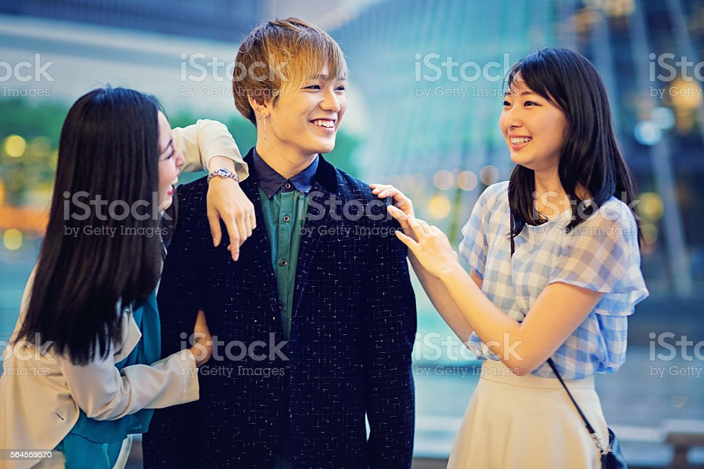 Two young Japanese girls are joking with a guy stock photo