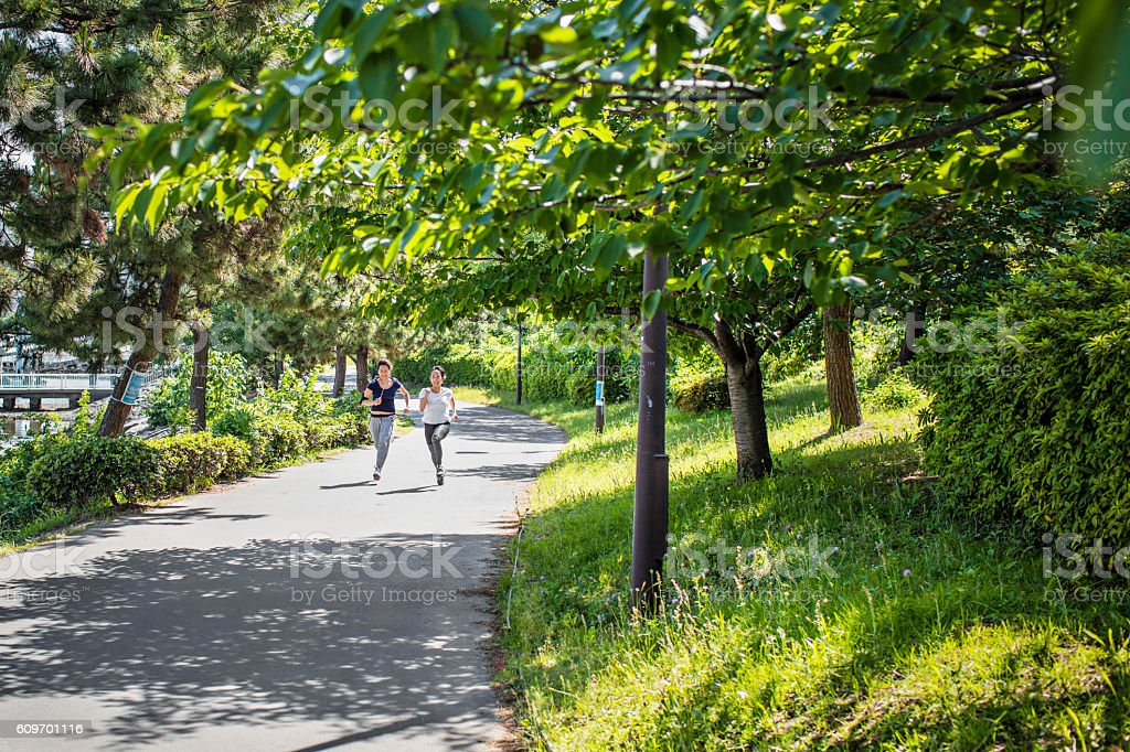 Two young Japanese women running in the park stock photo