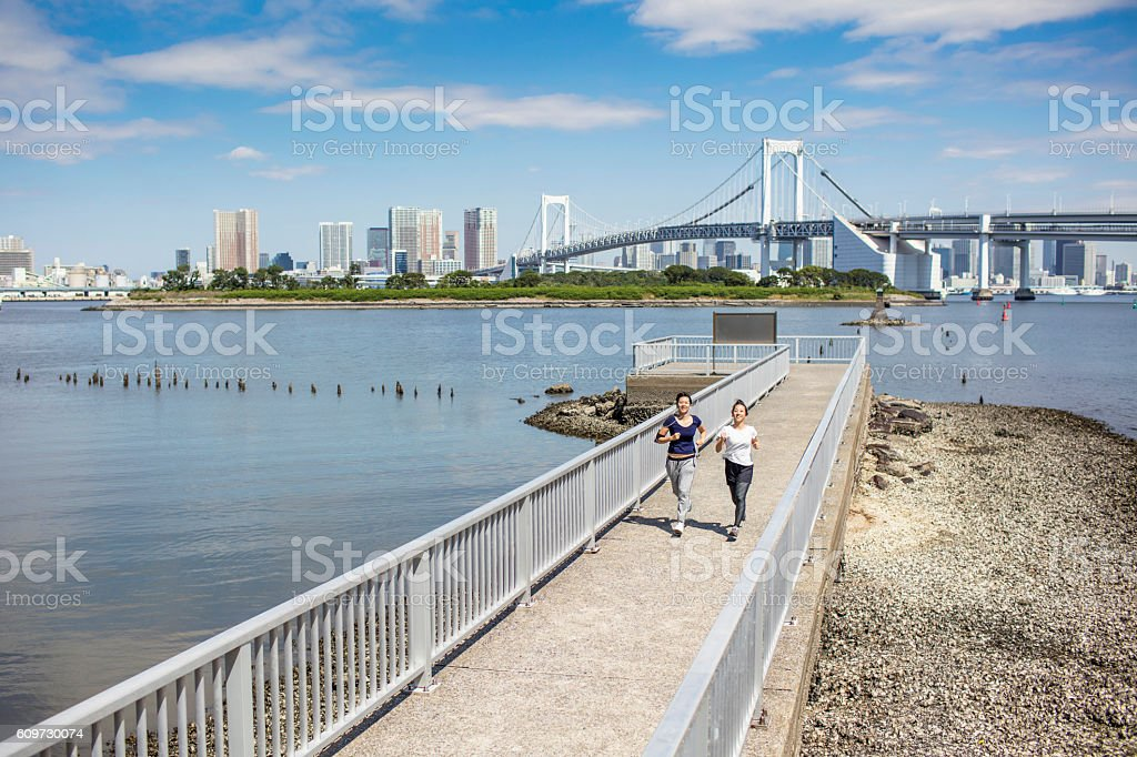 Two young Japanese women running in Tokyo stock photo