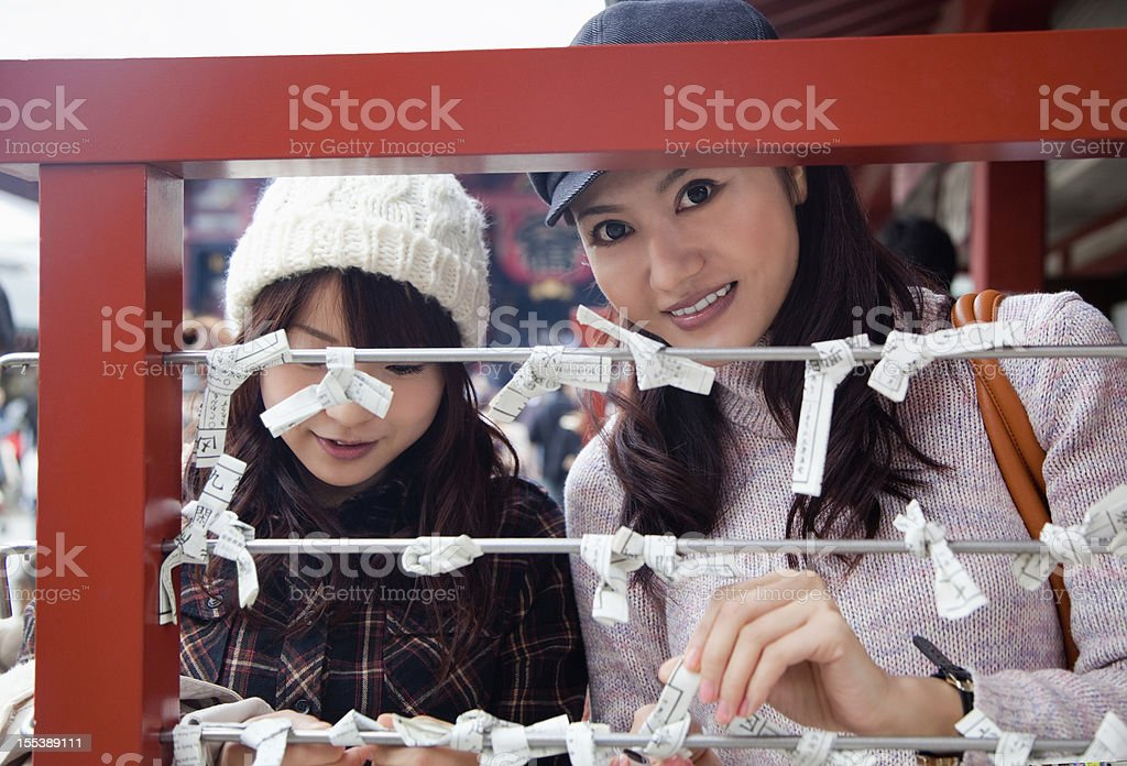 Two young Japanese women tying omikuji (fortune paper). stock photo