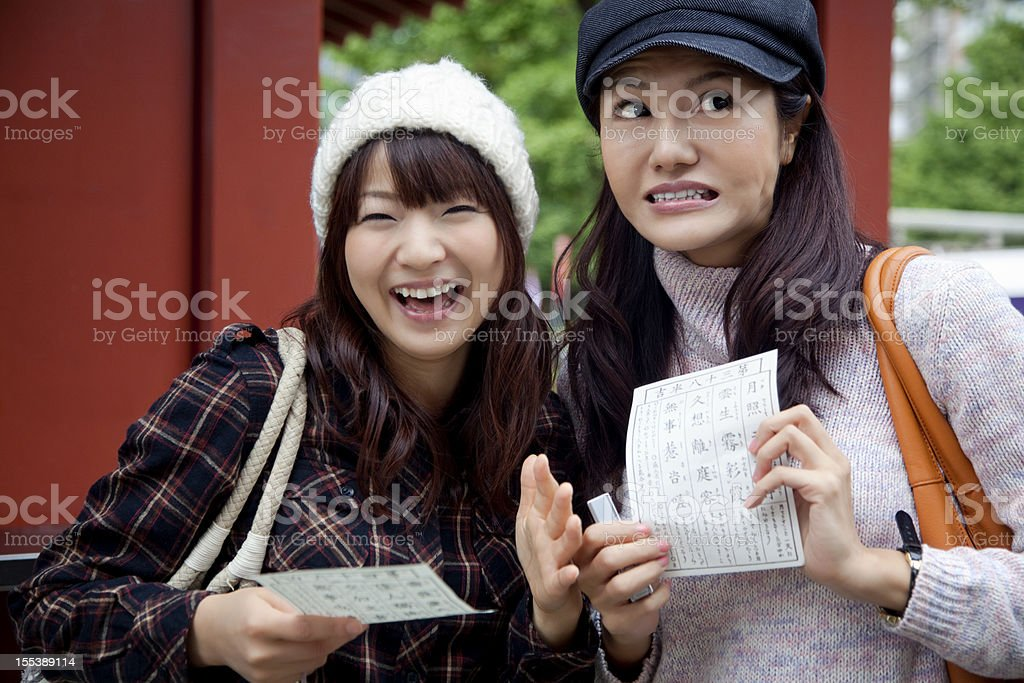 Two young Japanese women with good and bad fortune papers royalty-free stock photo