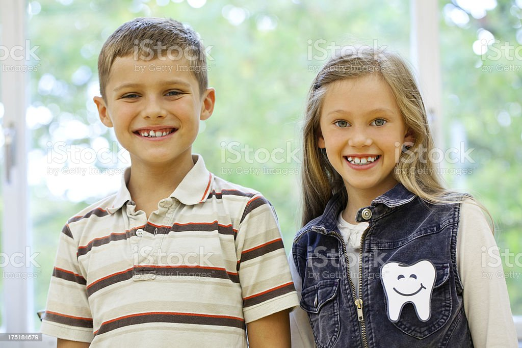 Two young kids coming out of the dentist stock photo