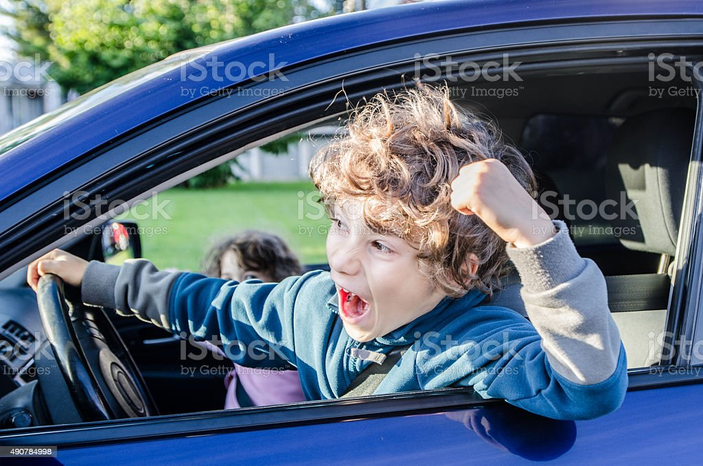 Two young kids driving a car with road rage stock photo