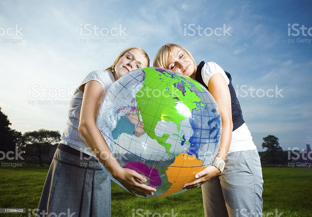 Two young ladies embracing inflatable globe royalty-free stock photo