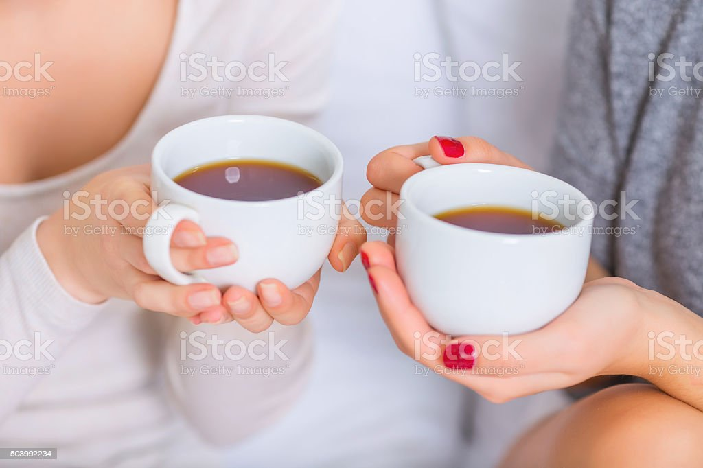 Two young ladies holding teacups stock photo