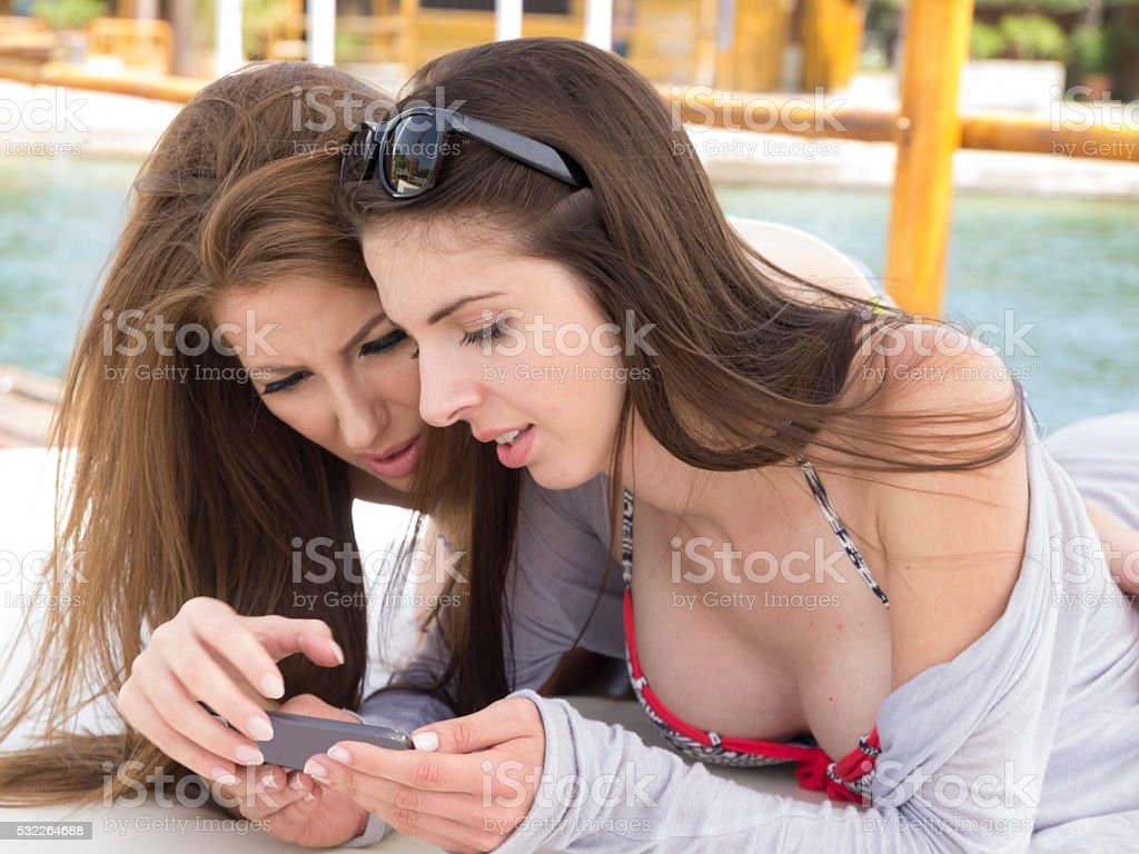 Two young ladies Playing the game over mobile on beach stock photo