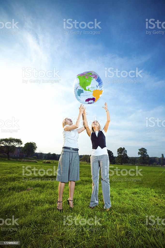 Two young ladies throwing up inflatable globe stock photo