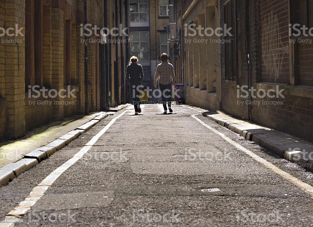 Two young lads walking down a long dark back alley stock photo