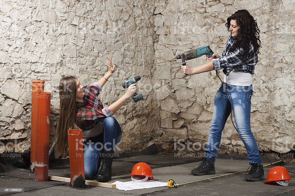 Two young long-haired woman with a drill and screwdriver stock photo