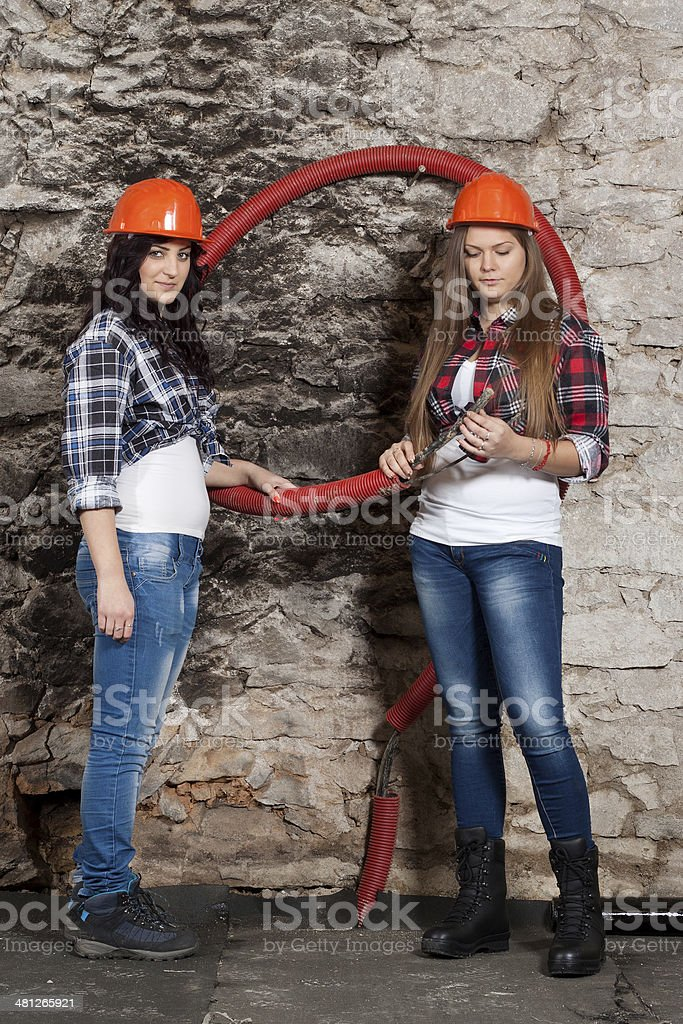 Two young long-haired woman with cables stock photo