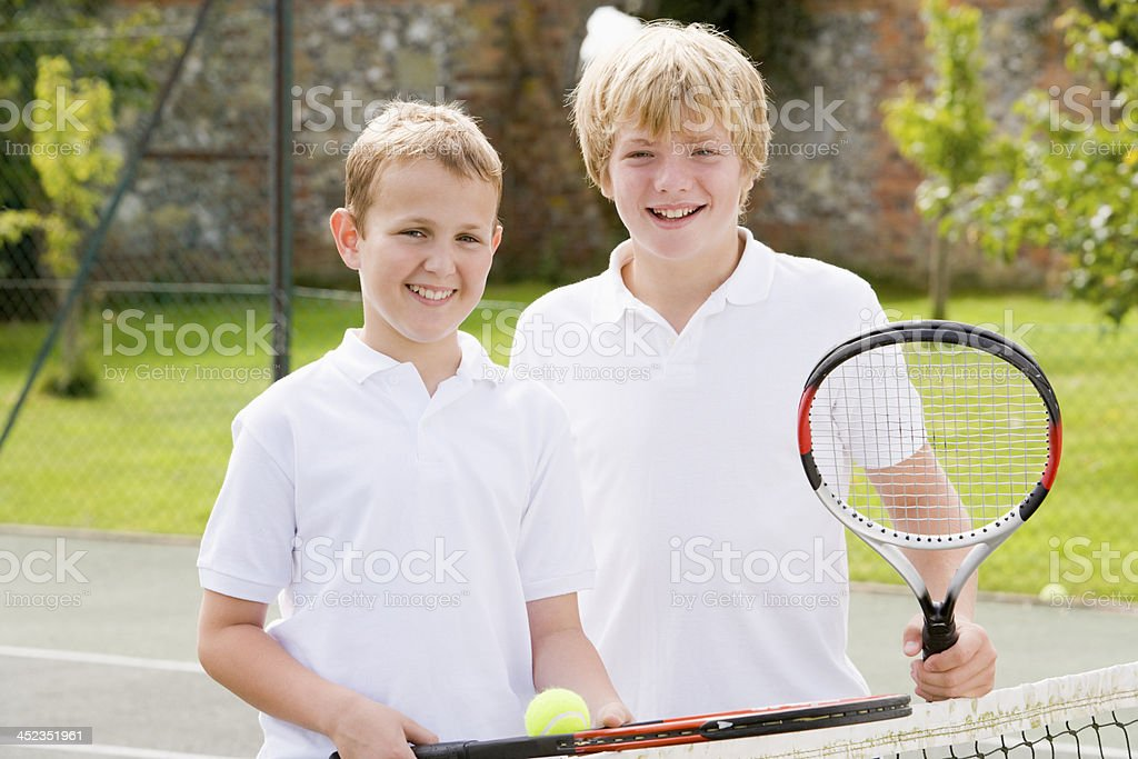 Two young male friends with rackets on tennis court smiling royalty-free stock photo